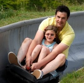 Father and daughter have a great family day out riding the toboggan at Woodlands Theme Park