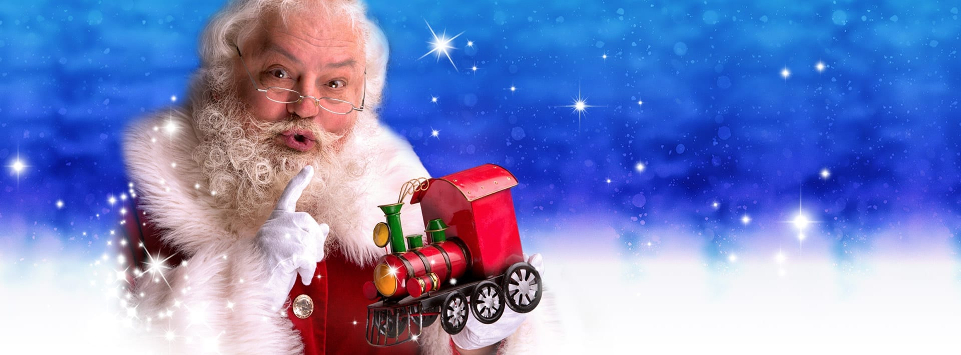 Santa saying 'shhh' to you whilst holding a toy train ready for our Christmas event in Devon